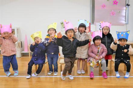 2歳児クラスの生徒が鬼の帽子をかぶって「鬼は外!」をしています。