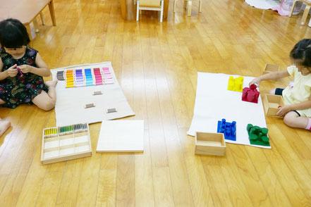 和紙の色に刺激されて、2人の幼稚園児が色板を使ったお仕事と、色つき円柱のお仕事に集中して取り組みました。
