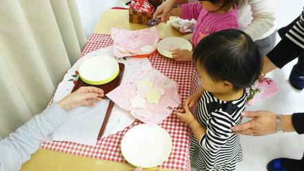 幼児教室でモンテッソーリ活動とリトミックを終えた後のおやつタイム。ひなまつりにちなんだおせんべいをトングでとって食べます。