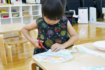 自分でつくった和紙の上にうちわの形の線が描かれています。その線に沿ってハサミで和紙を切ります。間違えないように集中して取り組みました。