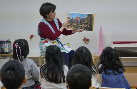 モンテッソーリの活動で、十二支の由来について幼稚園児が絵本に聞きいっています。1月1日にかみさまのもとに駆けつけた順番で干支が決まりました。