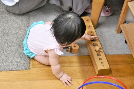 モンテッソーリの個別活動で、0歳児がはめ込み円柱の活動に集中しています。