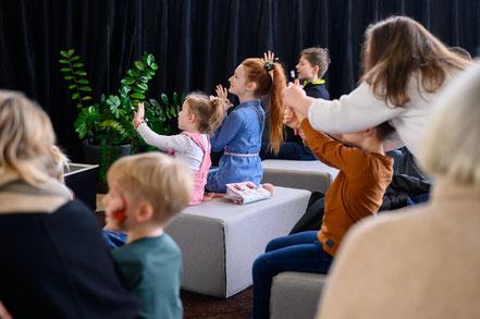 Magier Johannes zaubert gemeinsam mit mehreren Kindern im stehen