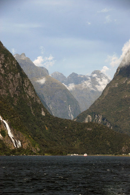 The staggering view back to the boat terminus at Milford Sound and the peaks of the Darran Mountains with their immensely steep slopes carvbed out of hard Plutonic rocks. Bowen Falls to the left.