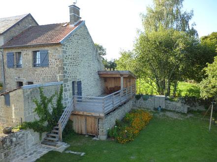 Gîte et grande terrasse de 35m² et salon de jardin couvert. Accès de plain-pied depuis le salon et escalier donnant sur le jardin.