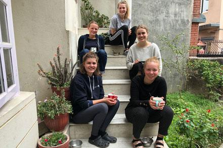 Da schien die Welt noch in Ordnung: Teepause der Volunteers Finia, Rosa, Laura, Linda und Sophie vor dem Apartment (von links vorne)