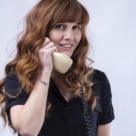 Anna hält einen antiquierten Telefonhörer ans Ohr.