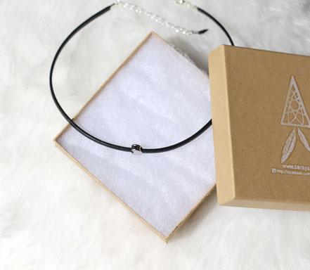 Collier ras du cou constitué d'une lanière de cuir véritable blanche de 3 mm de large, ornée d'une perle en forme de lune plaquée or.  Ce collier se termine par un fermoir mousqueton ainsi qu'une chaînette d'extension plaqués or avec finition mini plumeau