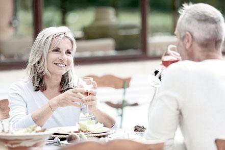 Pärchen mittleren Alters beim gemeinsamen Essen draußen mit Wein
