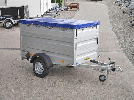 Humbaur PW Anhänger mit einem doppelten Bordwandaufsatz, darüber ist eine Flachplane montiert, der Anhänger wurde als Packet aufbereitet zum Kaufen