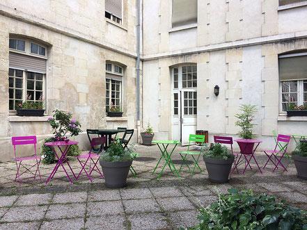 La terrasse du service de soins palliatifs aménagée avec un nouveau mobilier coloré et des jardinières et bacs plantés de fleurs dans un camaïeu de roses, de plantes olfactives et de feuillages aromatiques et doux.