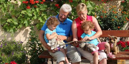 Opa und Oma mit Enkelkind auf Bauernhof