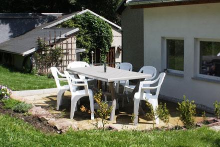 Sonnige Terrasse mit Tischgruppe und Grill