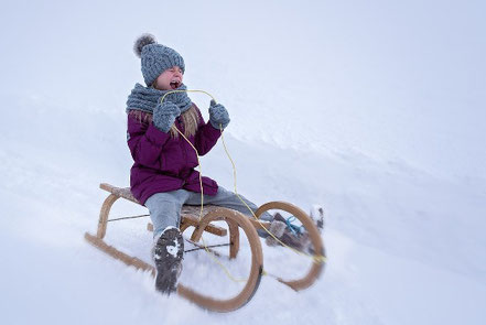 Mädchen auf Schlitten im Schnee