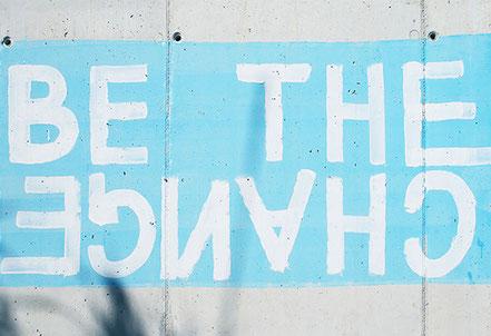 """Betonwand plakativ bemalt mit den Worten """"Be the Change"""", wobei """"Change"""" auf dem Kopf steht."""