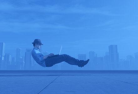 Mann schwebt über dem  Boden, mit Laptop auf den Knien. Lösungen für mehr Leichtigkeit.