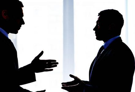 Konflikt am Arbeitsplatz zwischen zwei Männern. Sie gestikulieren. Konfliktfolgen im Unternehmen stoppen.