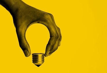 Hand hält Glühbirne. Coaching als Initiator für Erkenntnisse.