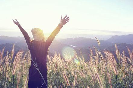 Lebensfreude ausstrahlende Frau. Zwischen Gräsern stehend, in eine ferne Berglandschaft schauend.