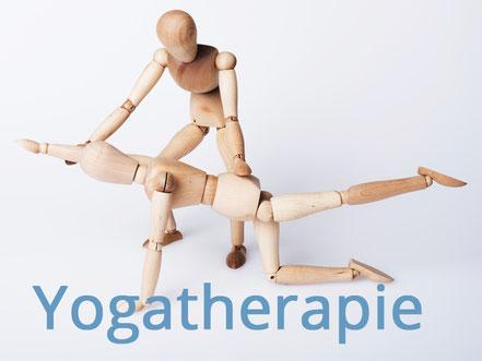 Zwei Holzpuppen stellen dar, wie ein Patient in der Yogatherapie bei einer Übung vom Yoga-Therapeuten unterstützt wird. Bild C. Schuessler/Fotolia