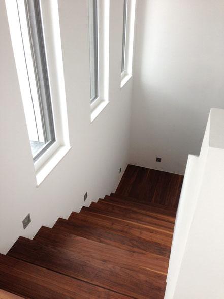 Treppenbereich mit dunklen Holzstufen und hohen Fenstern