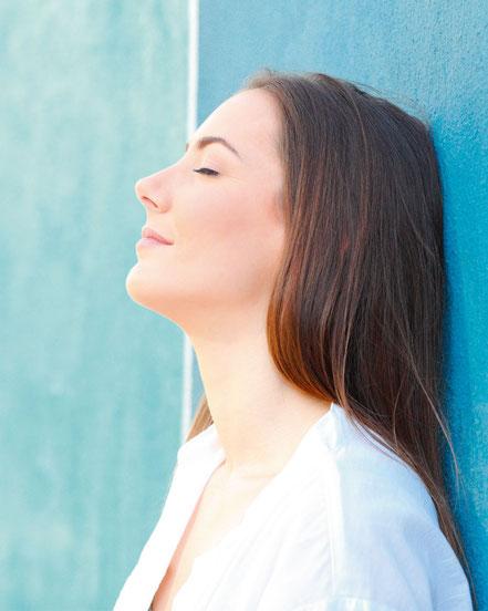 Frau lehnt versonnen an einer Wand und lässt sich die Sonne ins Gesicht scheinen.