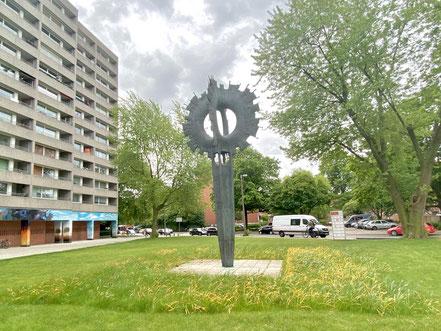 """Die Plastik """"Sonne"""" ist eingerahmt ins Kattenturmer Stadtbild, bestehend aus der Großraumbebauung und einer Ladenzeile am Sonnenplatz (Foto: 05-2020, Jens Schmidt)"""
