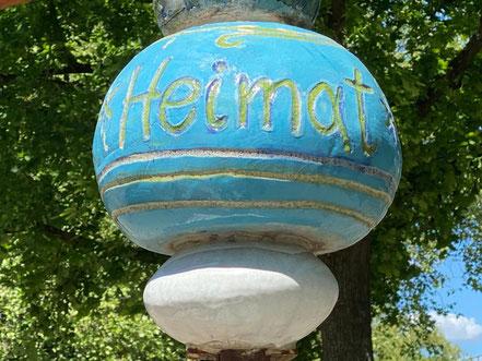 """""""Heimat"""" steht auf einer der Kugeln, die eine von fünf Stelen des Kunstwerks """"Vom Gehen und Kommen"""" bilden. Kunst im öffentlichen Raum in Bremen Obervieland (Foto: 05-2020, Jens Schmidt)"""