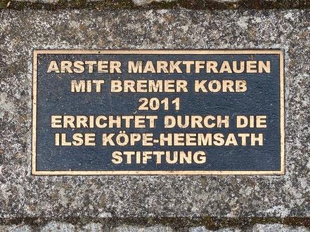 """Inschrift der Bronzeplastik """"Arster Marktfrauen mit Bremer Korb 2011, erreichtet durch die Ilse Köpe-Heemsatz Stiftung"""" (Foto: 05-2020, Jens Schmidt)"""