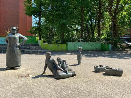 """Das Kunstwerk """"Erdbeerpflückerin mit Kindern"""" befindet sich auf einem gepflasterten Platz vor zwei Großwohnanlagen in Bremen-Arsten (Foto: 05-2020, Jens Schmidt)"""
