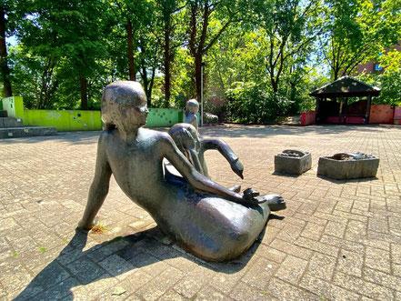 """Eine der Kinder-Figuren, ein jugendliches Mädchen, sitzt mit ihrem kleinen Bruder auf dem Boden. Das Mädchen hat eine Schnecke in der Hand, die die Aufmerksamkeit des Jungen auf sich zieht. """"Erdbeerpflückerin mit Kindern"""" (Foto: 05-2020, Jens Schmidt)"""