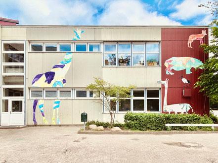 Verschiedene übergroße Bilder phantasievoll colorierter afrikanischer Wildtiere an den Gebäuden der Grundschule Alfred-Faust-Straße in Bremen-Kattenesch, Bremen Obervieland (Foto: 05-2020, Jens Schmidt)