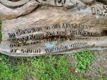 """Die Inschrift """"Im Gedenken an alle Menschen, die vor Krieg, Not und Verfolgung flohen und auf dem Weg zu uns ihr Leben verloren haben"""" auf dem Kunstwerk """"Teppich"""" von Klaus Effern (Foto: 05-2020, Jens Schmidt)"""