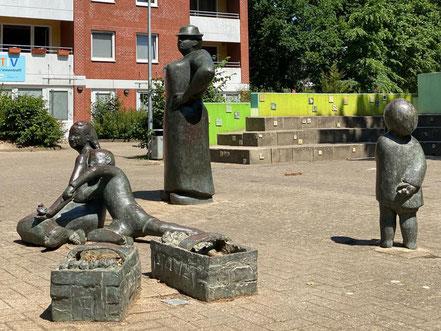 """Bronzeplastik """"Erdbeerpflückerin mit Kindern"""" - 1982 in Bremen-Arsten installiertes Kunstwerk im öffentlichen Raum (Foto: 05-2020, Jens Schmidt)"""