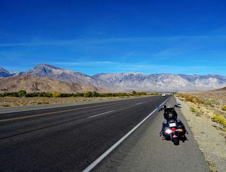 Motoglobe Motorradreisen. Die Harlex steht am Strasserand und die Strasse zieht sich in einer langen geraden Schnur bis zu den Sierra Nevadas im Hintergrund.