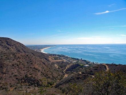Motoglobe Motorradreisen. Vor uns liegt die Küste mit der Ortschaft Malibu, Stränden, Hügel und Meer in Kalifornien, USA.