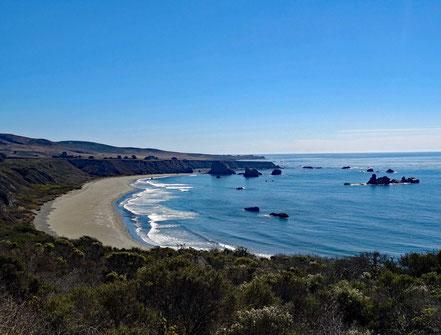 Motoglobe Motorradreisen. Eine schöne Bucht mit weissen Strand liegt vor uns umgeben von Felsen und blauem Meer.