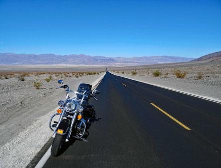 Motoglobe Motorradreisen. Die Harley steht auf der Nr. 190 und wir blicken zurück auf die lange gerade Strecke durch die Wüstenlandschaft des Death Valley.