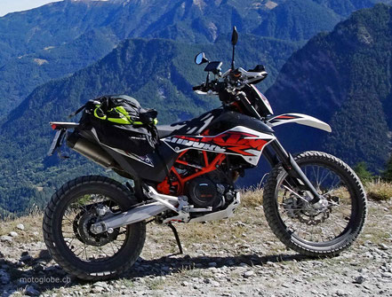 Motoglobe Motorradreisen. Ein rot schwarze KTM 690 Enduro R steht auf einer Schotterstrasse.