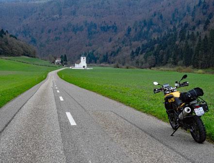 Motorradreisen; Die BMW f800GS steht auf der Strasse von Saint-Ursanne nach Saint-Hippolyte und wir sehen eine weisse Kirche und grüne Wiesen und Wald.