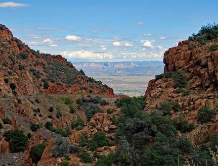 Motoglobe Motorradreisen. Durch rote Felsen führt die Strasse talwärts zur schön gelegenen Ortschaft Jerome, Arizona, USA