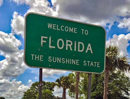Motoglobe_Motorradreisen. Die grosse grüne Tafel mit dem Willkommensgruss für alle Reisende nach Florida weist diverse Schusslöcher auf.