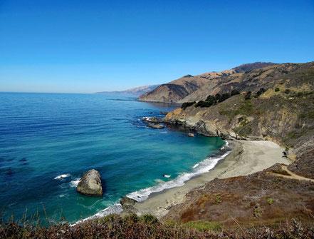Motoglobe Motorradreisen. Der schöne Strand liegt in einer Bucht eingebetet zwischen Felsen und das blaue Meer leuchtet.