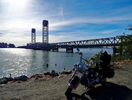 Motoglobe Motorradreisen. Die Harley steht in der Ortschaft Rio Vista am Sacramento Fluss und im Hinergrund ist die Rio Visto Brücke zu sehen.