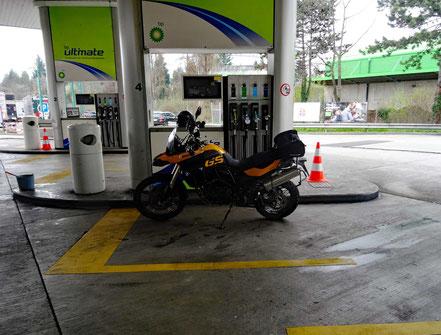 Motorradreisen; Die BMW f800 GS steht vor eine Tanksäule und wir vollgetankt auf der Raststätte Pratteln bei Basel.