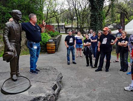 Motoglobe_Motorradreisen. Der Führer der Führung durch die Jack Daniels Distillery steht neben eine Broncefigur des Gründers Jack Daniels.