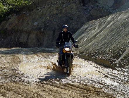 Motorradreisen Motorrad fährt durch eine Wasserpfütze in der Kiesgrube