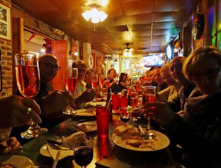 Motoglobe_Motorradreisen. Viele Leute sitzen an einem Tisch im Restaurant und haben Essensteller vor sich auf dem Tisch und prosten sich alle mit einem Glas zu.