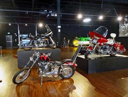 Motoglobe_Motorradreisen. Ein Motorradchopper, Road Kind und andere Harely Davidson Maschinen, stehen in einer Halle mit Licht.