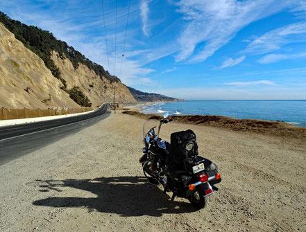 Motoglobe Motorradreisen. Die Harley steht auf einem Kiesparkplatz neben dem Highway Nr. 1 in Kalifornien und vor der Harley ist das Meer.